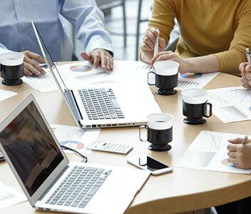 PM、PL、PMOといったポジションで、ノートパソコンと資料をみながらマネジメントコンサルティングを行なっている写真